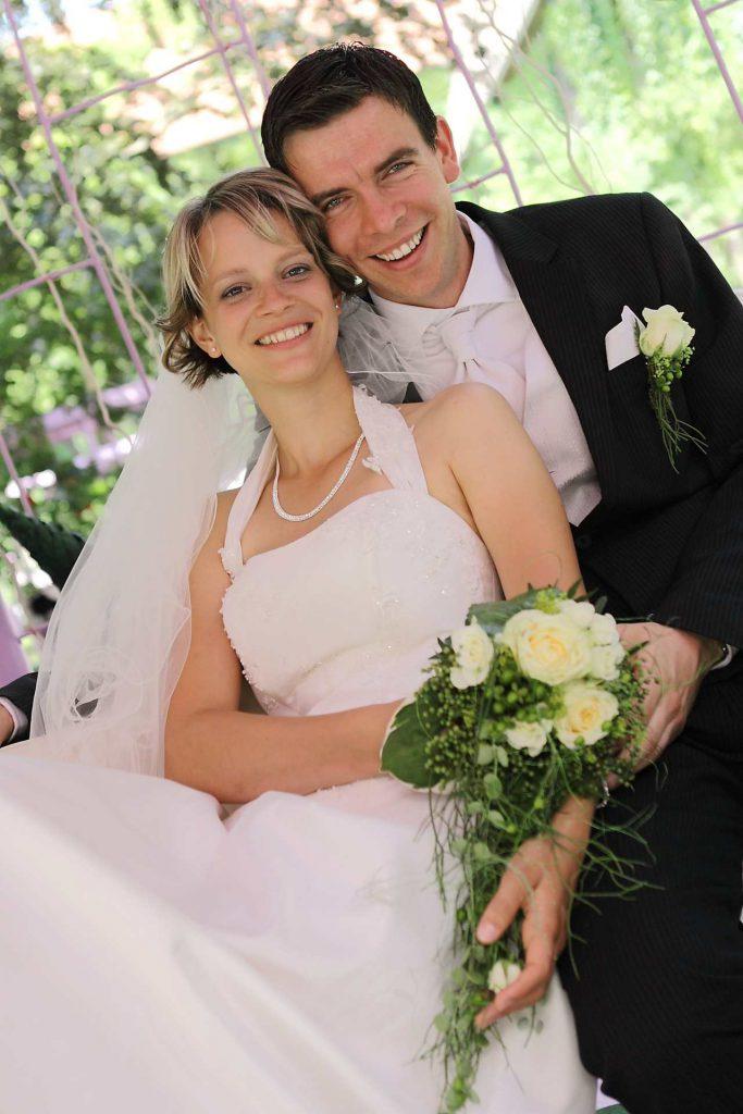 Elegante Hochzeit in Halle - Brautpaar lächelt sitzend in Kamera