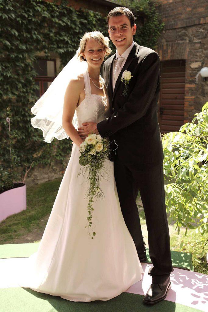 Elegante Hochzeit in Halle - Brautpaar lächelt stehend in Kamera