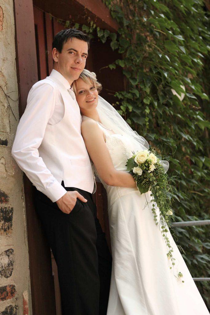 Brautpaar lehnt sich an Tür an