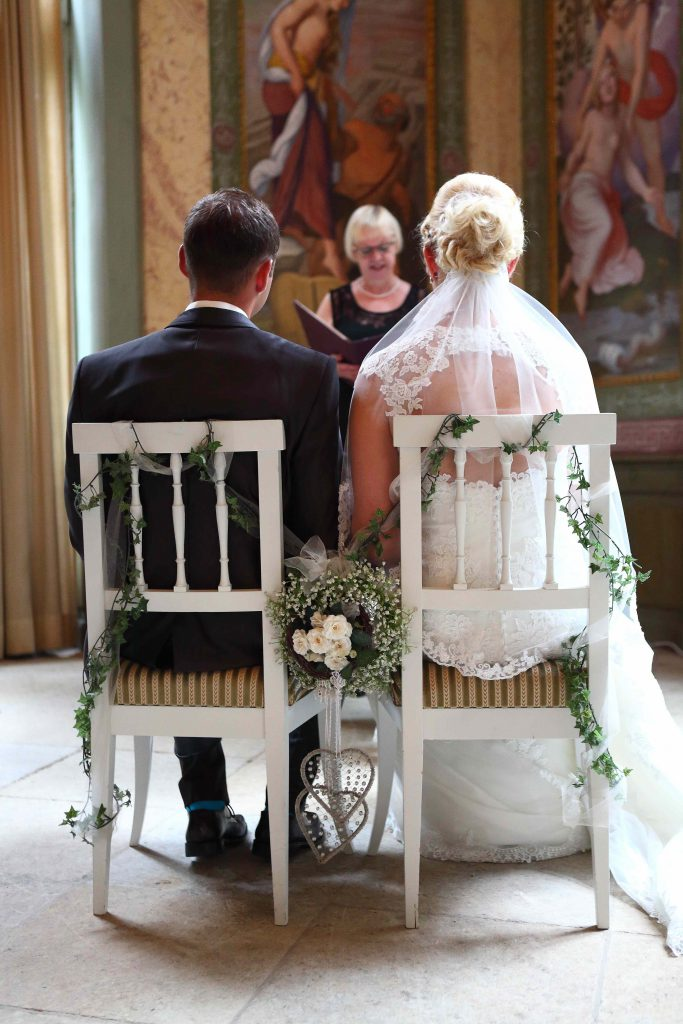 Brautpaar sitzend auf Stühlen - Foto von hinten