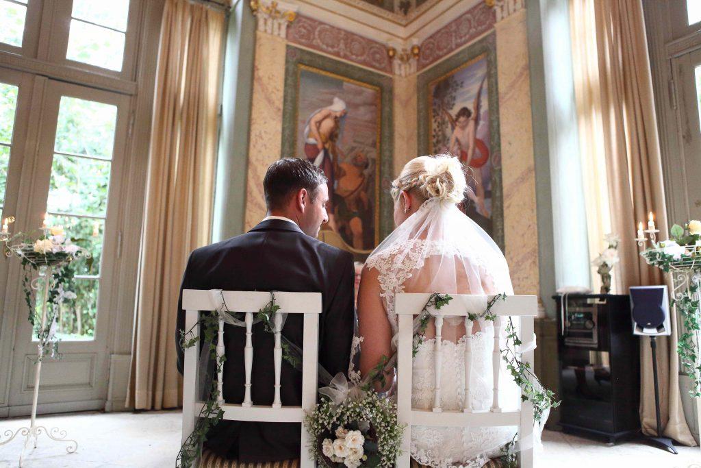 Brautpaar sitzend auf Stühlen - Foto von hinten unten