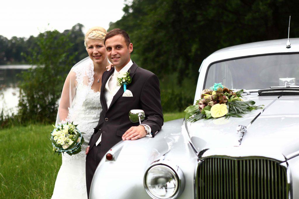 Brautpaar lehnt an Hochzeitsauto