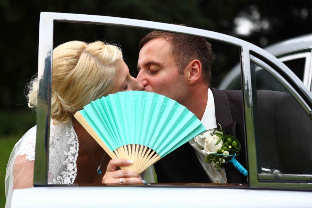 Brautpaar küsst sich hinter Fächer