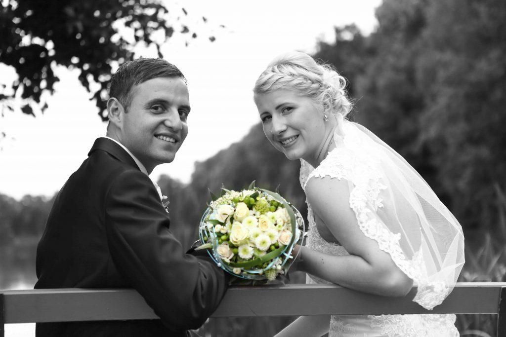 Brautpaar auf Bank lächelt in Kamera