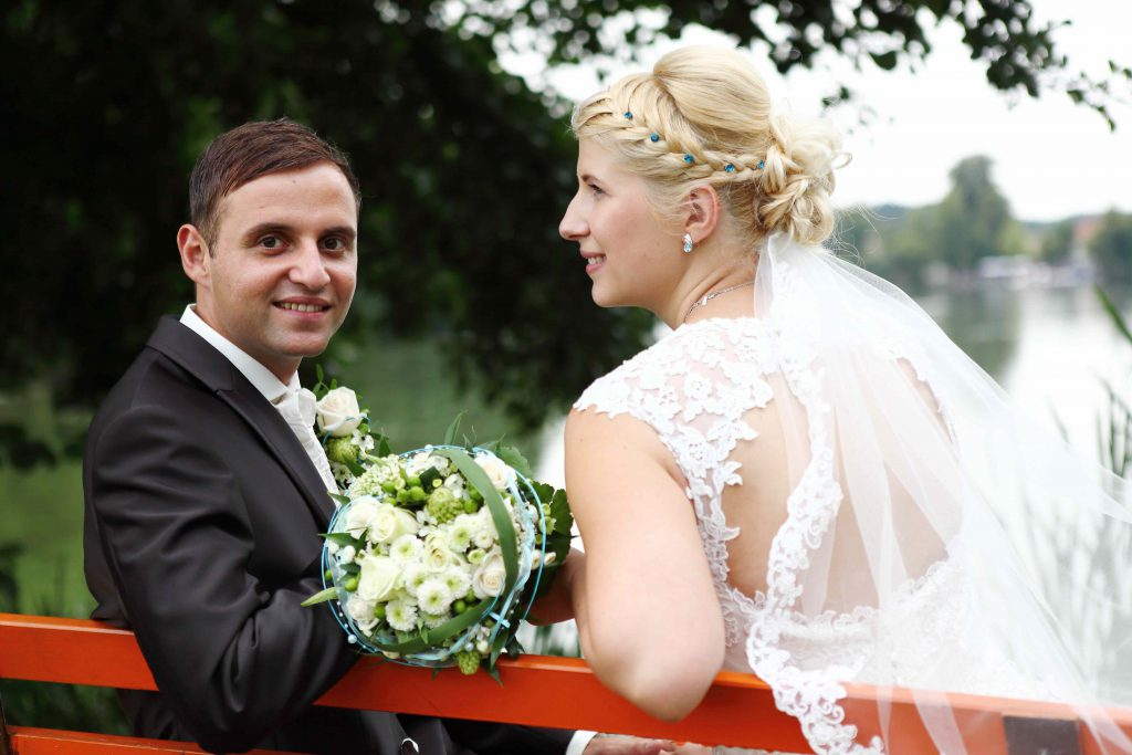 Brautpaar auf Bank, Bräutigam lächelt in Kamera