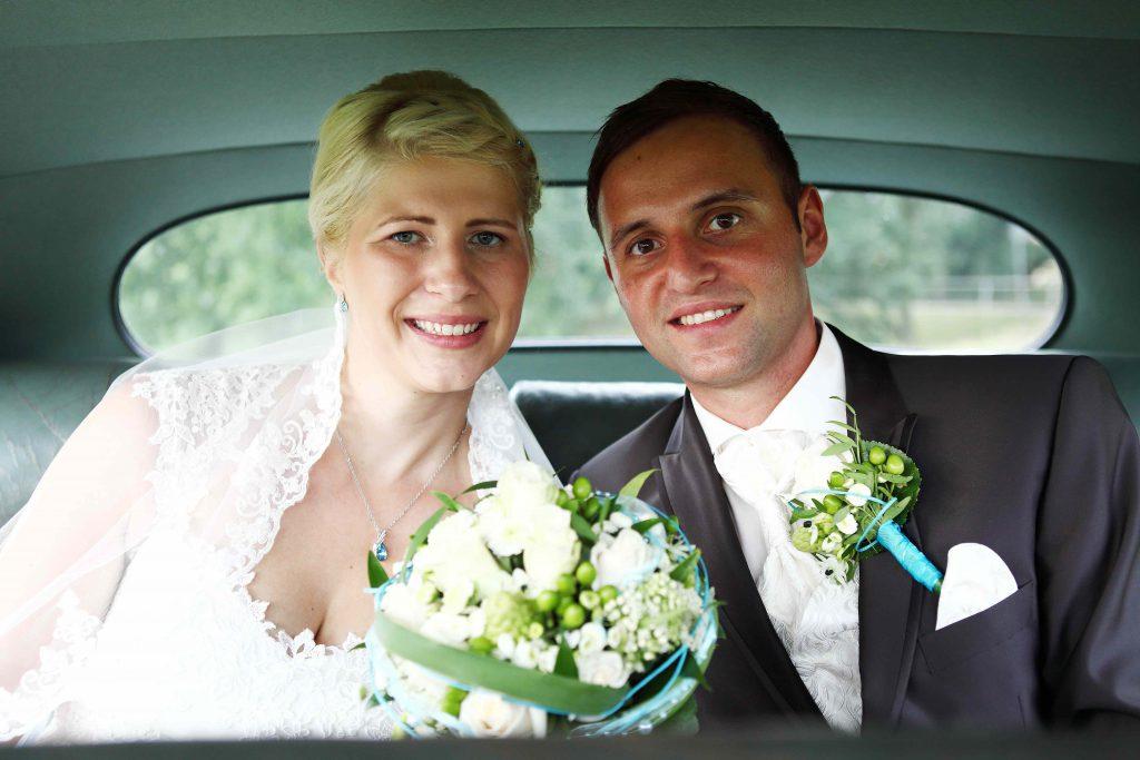 Brautpaar sitzt auf Rücksitz im Auto