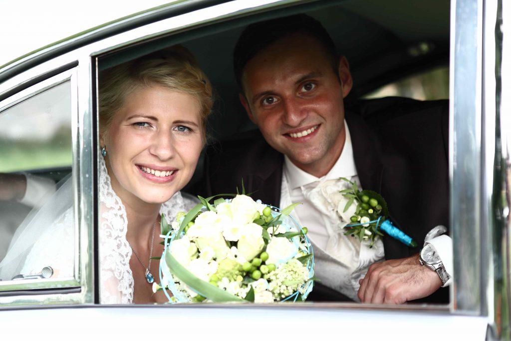 Brautpaar schaut aus SEitenfenster des Autos heraus
