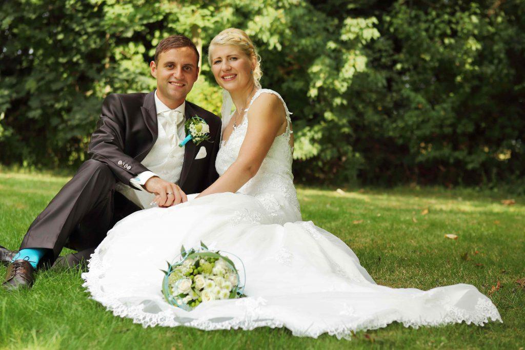 Brautpaarfoto - sitzend im Gras