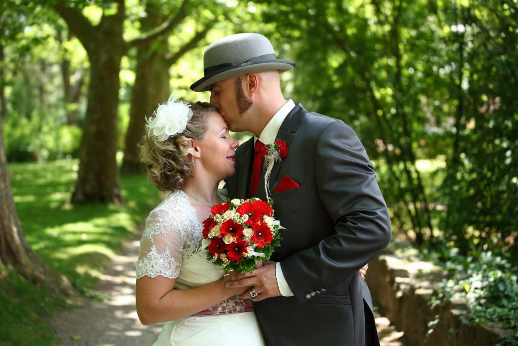 Bräutigam mit Melone küsst Braut