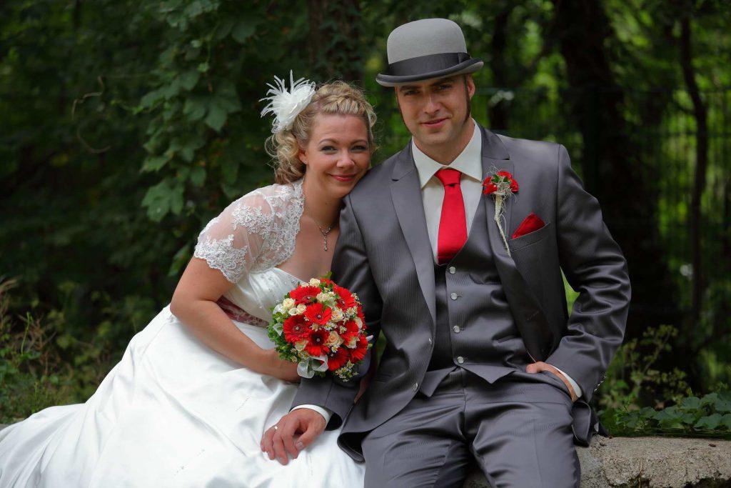 Brautpaar sitzt auf Steinmauer