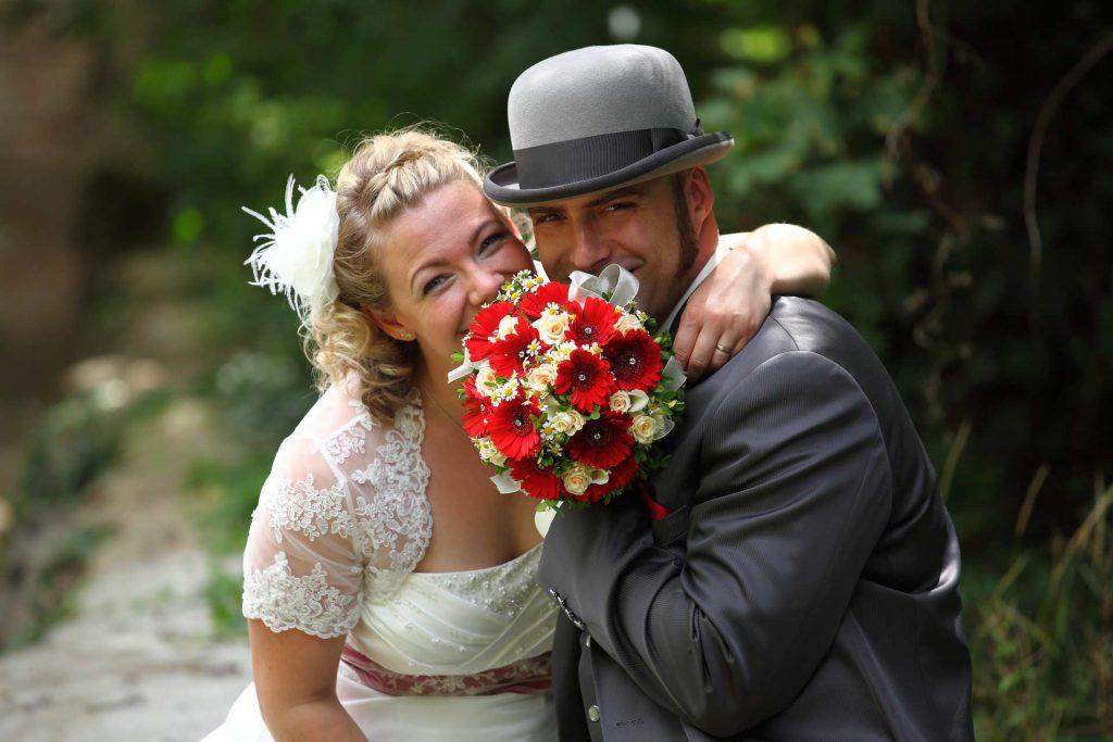 Brautpaar lächelt hinter Brautstrauß hervor