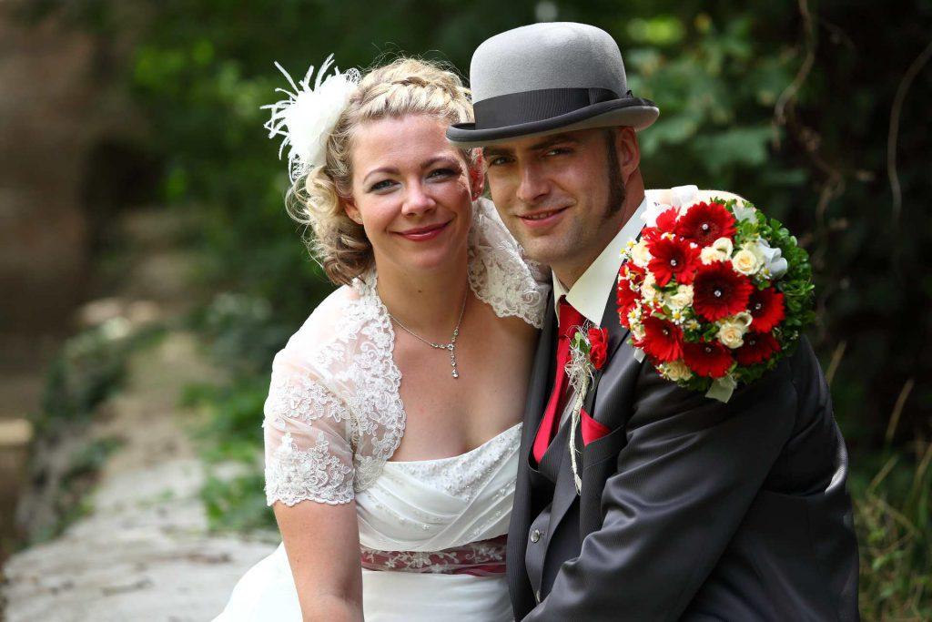 Brautpaar lächelt sitzend in die Kamera