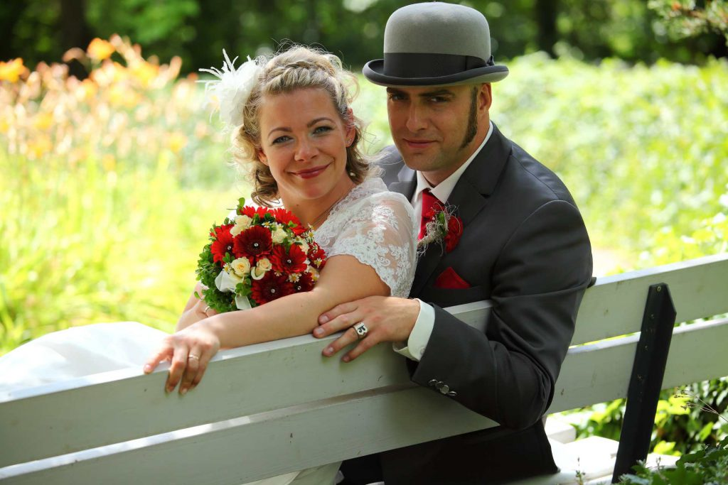 Brautpaar lächelt sitzend auf einer Parkbank