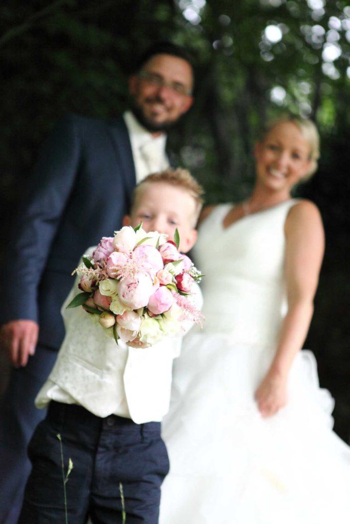 Hochzeitspaar mit Kind und Strauß