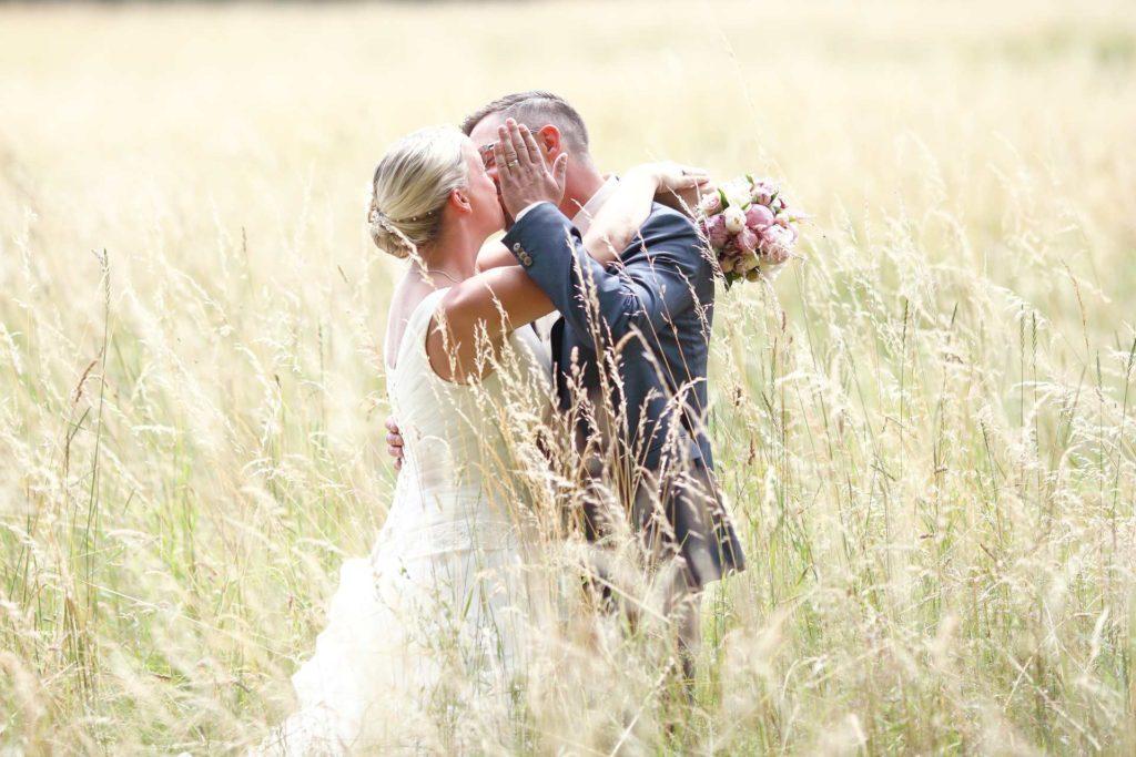 Hochzeitspaar im hohen Gras und Kuss