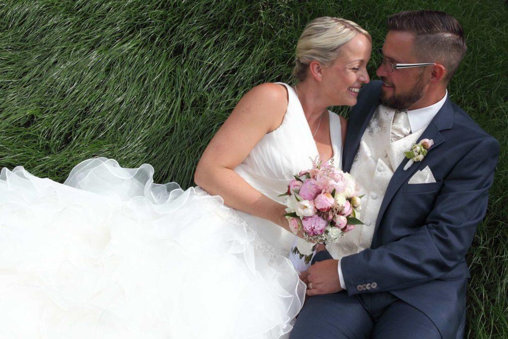 Hochzeitspaar auf grünem Gras