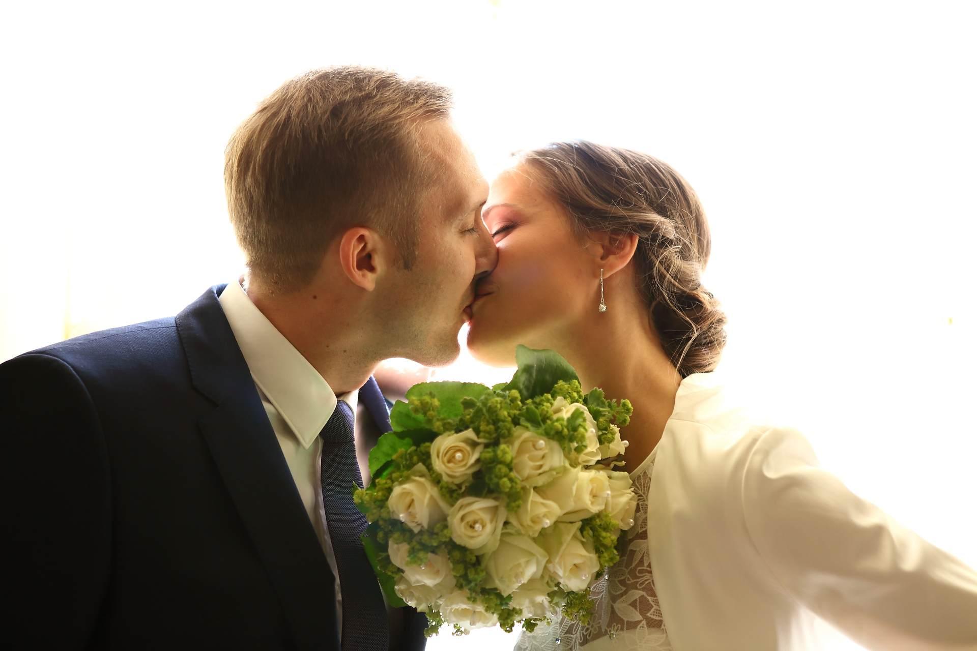 Hochzeitsfotos in Leipzig - Hochzeitspaar küsst sich vor dem Fenster
