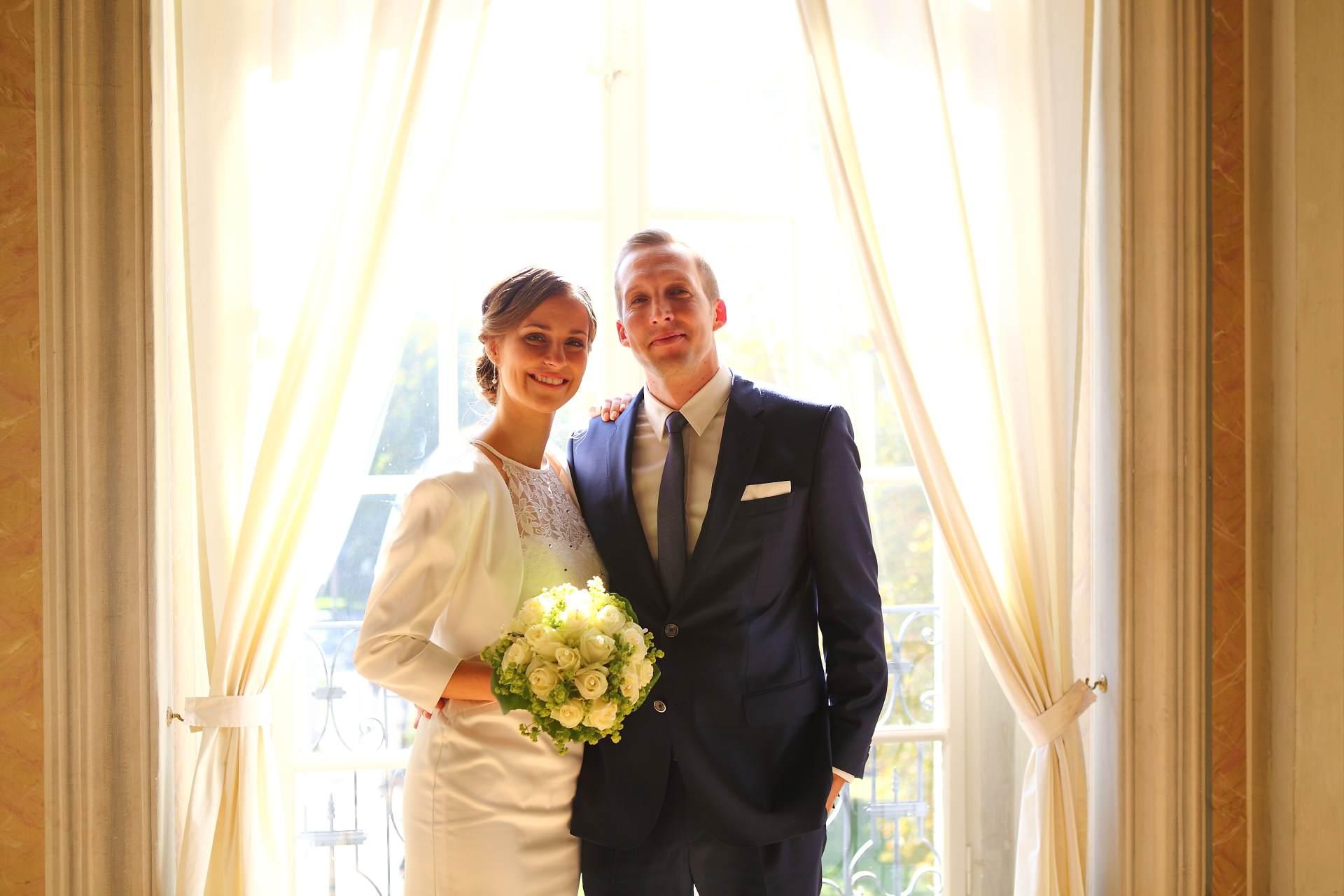 Hochzeitsfotos in Leipzig - Hochzeitspaar mit Brautstrauß vor dem Fenster
