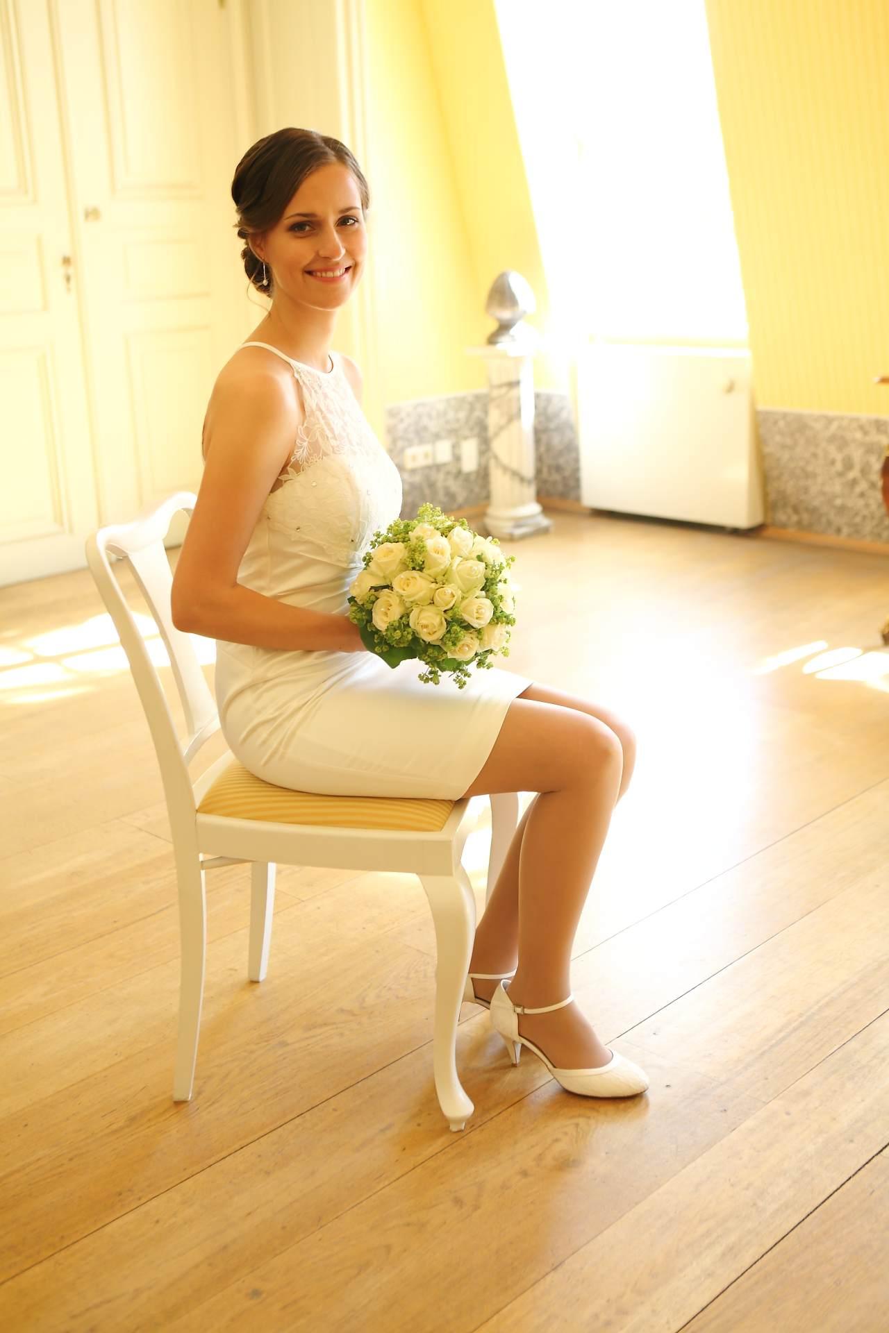 Hochzeitsfotos in Leipzig - Braut sitzend mit Blumenstrauß