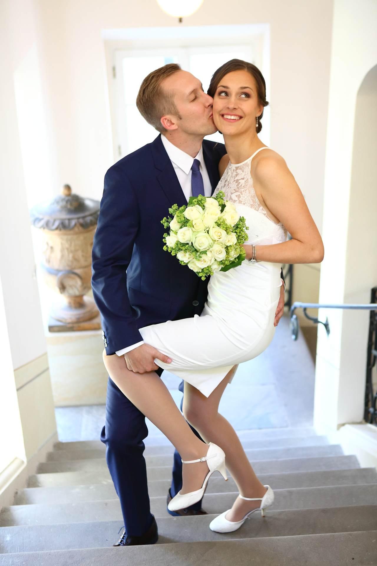 Hochzeitsfotos in Leipzig - Bräutigam küsst Braut auf Treppe