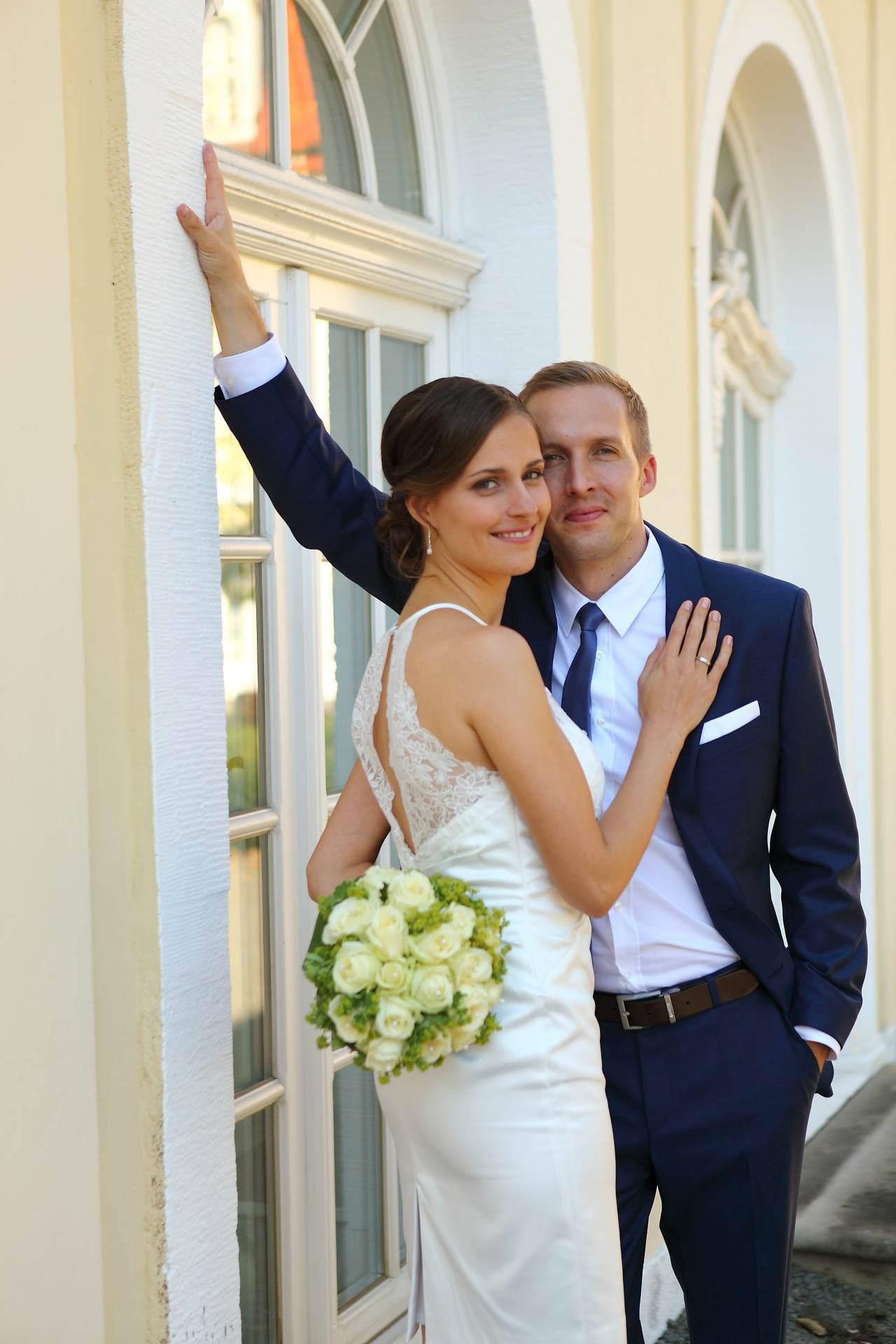 Hochzeitsfotos in Leipzig - Hochzeitspaar lehnt an der Mauer und schaut in Kamera