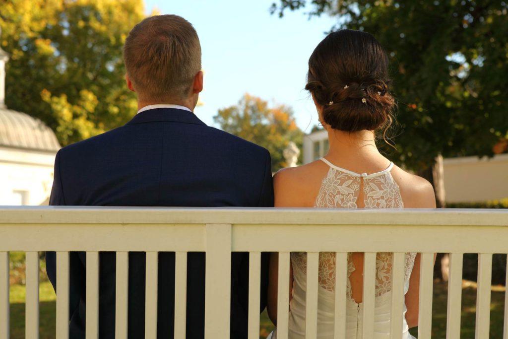 Hochzeitspaar von hinten auf einer Bank